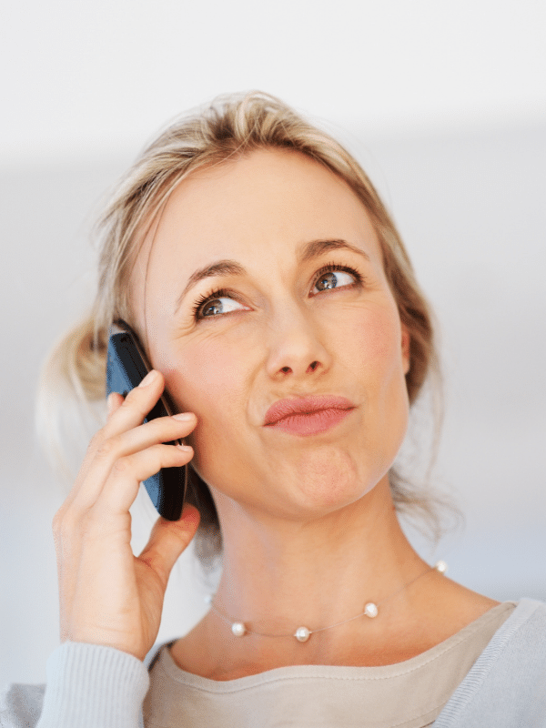 Woman holding phone looking annoyed