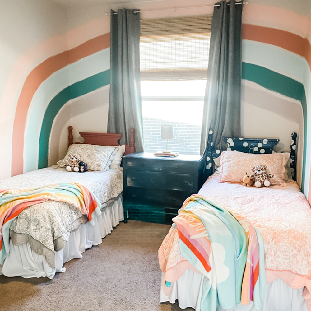 two twin beds with dresser and rainbow painted walls